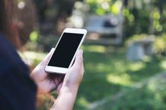Εικόνα προτύπων μιας γυναίκας που κρατά και που χρησιμοποιεί το άσπρο έξυπνο τηλέφωνο με την κενή μαύρη οθόνη στην υπαίθρια και π Στοκ φωτογραφία με δικαίωμα ελεύθερης χρήσης