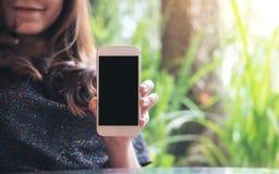 Εικόνα προτύπων μιας όμορφης γυναίκας που κρατά και που παρουσιάζει άσπρο κινητό τηλέφωνο με την κενή μαύρη οθόνη στο εστιατόριο Στοκ φωτογραφία με δικαίωμα ελεύθερης χρήσης