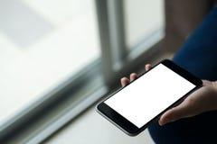 Εικόνα προτύπων του χεριού γυναικών ` s που κρατά το μαύρο κινητό τηλέφωνο με την κενή άσπρη οθόνη στο μηρό με το άσπρο πάτωμα κε Στοκ Εικόνες