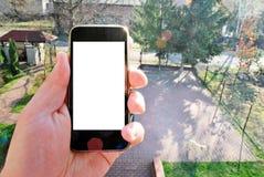 Εικόνα προτύπων του χεριού που κρατά το μαύρο κινητό τηλέφωνο με την κενή άσπρη οθόνη και το πράσινο δάσος δέντρων, υπόβαθρο φύση Στοκ φωτογραφία με δικαίωμα ελεύθερης χρήσης