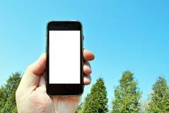 Εικόνα προτύπων του χεριού που κρατά το μαύρο κινητό τηλέφωνο με την κενή άσπρη οθόνη και το πράσινο δάσος δέντρων, υπόβαθρο φύση Στοκ Εικόνες