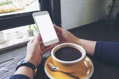 Εικόνα προτύπων των χεριών γυναικών ` s που κρατά το άσπρο κινητό τηλέφωνο με την κενή οθόνη και το κίτρινο φλυτζάνι καφέ Στοκ Φωτογραφίες