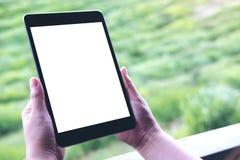 Εικόνα προτύπων των χεριών γυναικών ` s που κρατά το μαύρο PC ταμπλετών με την κενή άσπρη οθόνη Στοκ Εικόνες