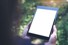 Εικόνα προτύπων των χεριών γυναικών ` s που κρατά το μαύρο PC ταμπλετών με την κενή άσπρη οθόνη και την πράσινη φύση Στοκ Εικόνα