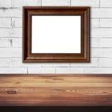 Εικόνα πλαισίων στον άσπρο τουβλότοιχο και το ξύλινο επιτραπέζιο υπόβαθρο Στοκ φωτογραφία με δικαίωμα ελεύθερης χρήσης