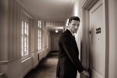 Εικόνα σεπιών του όμορφου ατόμου στο κοστούμι στο διάδρομο ξενοδοχείων που χρησιμοποιεί τη βασική κάρτα στην ανοικτή πόρτα δωματί στοκ φωτογραφίες