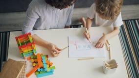 Εικόνα σχεδίων μητέρων και γιων που χρωματίζει έπειτα την με τα μολύβια στον πίνακα στο σπίτι φιλμ μικρού μήκους