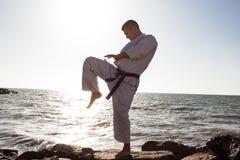 Εικόνα της αρσενικής karate τοποθέτησης μαχητών στο υπόβαθρο θάλασσας πετρών Στοκ Φωτογραφία