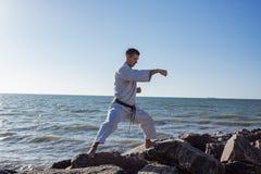 Εικόνα της αρσενικής karate τοποθέτησης μαχητών στο υπόβαθρο θάλασσας πετρών Στοκ φωτογραφία με δικαίωμα ελεύθερης χρήσης