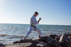 Εικόνα της αρσενικής karate τοποθέτησης μαχητών στο υπόβαθρο θάλασσας πετρών Στοκ εικόνα με δικαίωμα ελεύθερης χρήσης