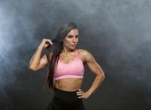 Εικόνα της γυναίκας ικανότητας στον αθλητισμό που ντύνει στον καπνό Νέο θηλυκό πρότυπο με το μυϊκό σώμα Οριζόντιος πυροβολισμός σ Στοκ Εικόνες