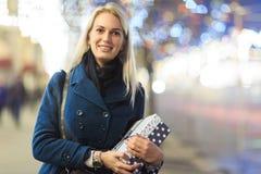 Εικόνα της γυναίκας στο παλτό με το δώρο στο κιβώτιο στοκ εικόνες