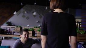 Εικόνα της λεπτής νέας γυναίκας στο μαύρο φόρεμα που περπατά μέσω του καφέ στους φίλους της Επιχείρηση των ανθρώπων που κάθονται  απόθεμα βίντεο