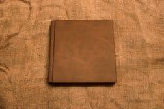 Εικόνα της καφετιάς κάλυψης λευκωμάτων φωτογραφιών δέρματος στο υπόβαθρο γιούτας Κ Στοκ εικόνες με δικαίωμα ελεύθερης χρήσης