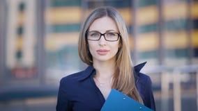 Εικόνα της μακρυμάλλους γυναίκας στην μπλε μπλούζα που στέκεται έξω με να ενσωματώσει το υπόβαθρο και την εξέταση τη κάμερα απόθεμα βίντεο