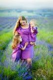 Εικόνα της νέας μητέρας που αγκαλιάζει δύο μικρά παιδιά, πορτρέτο κινηματογραφήσεων σε πρώτο πλάνο της ευτυχούς οικογένειας, χαρι στοκ εικόνα