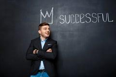 Εικόνα του ατόμου πέρα από τον πίνακα με την κορώνα και του κειμένου επιτυχούς στοκ εικόνα