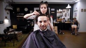 Εικόνα του γενειοφόρου τύπου στο barbershop που καλύπτεται με το μαύρο peignoir Θηλυκός κουρέας στα περιστασιακά ενδύματα που κάν απόθεμα βίντεο