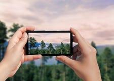 Εικόνα του δάσους στη Νορβηγία στο κινητό τηλέφωνο Θηλυκός πάρτε τα δέντρα εικόνων στο υπόβαθρο βουνών και λιμνών στο κινητό τηλέ Στοκ φωτογραφίες με δικαίωμα ελεύθερης χρήσης