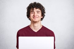 Εικόνα του ελκυστικού νέου τύπου με τη σγουρή τρίχα που φορά την περιστασιακή καφέ μπλούζα, καθμένος μπροστά από το ανοικτό lap-t στοκ φωτογραφίες