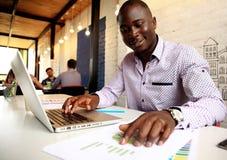 Εικόνα του επιχειρηματία αφροαμερικάνων που εργάζεται στο lap-top του Όμορφος νεαρός άνδρας στο γραφείο του Στοκ Φωτογραφία