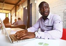 Εικόνα του επιχειρηματία αφροαμερικάνων που εργάζεται στο lap-top του Όμορφος νεαρός άνδρας στο γραφείο του Στοκ εικόνα με δικαίωμα ελεύθερης χρήσης