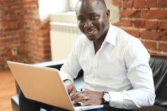 Εικόνα του επιχειρηματία αφροαμερικάνων που εργάζεται στο lap-top του Όμορφος νεαρός άνδρας στο γραφείο του Στοκ Εικόνα