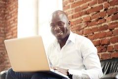 Εικόνα του επιχειρηματία αφροαμερικάνων που εργάζεται στο lap-top του Όμορφος νεαρός άνδρας στο γραφείο του Στοκ Εικόνες