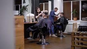 Εικόνα του εσωτερικού barbershop και δύο επαγγελματικών hairstylists Θηλυκοί και αρσενικοί κουρείς που εργάζονται με το κάθισμα π φιλμ μικρού μήκους
