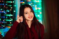 Εικόνα του ευτυχούς εύθυμου όμορφου χαμόγελου μορίων κοριτσιών άσπρου αρκετά στο στούντιο με τα φω'τα Χριστουγέννων Όμορφο χαμογε Στοκ Φωτογραφίες