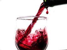 Εικόνα του κρασιού χύνοντας στο γυαλί κρασιού που απομονώνεται στο λευκό στοκ εικόνες