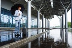 Εικόνα του νέου κοκκινομάλλους επιχειρηματία που κρατά τη μαύρη ομπρέλα στη βροχή στο τερματικό Στοκ φωτογραφίες με δικαίωμα ελεύθερης χρήσης