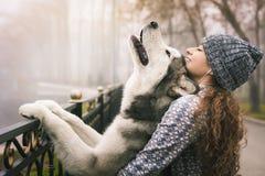 Εικόνα του νέου κοριτσιού με το σκυλί της, από την Αλάσκα malamute, υπαίθριο Στοκ εικόνα με δικαίωμα ελεύθερης χρήσης