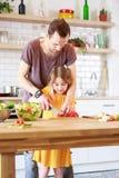 Εικόνα του πατέρα με λίγη μαγειρεύοντας σαλάτα κορών Στοκ Εικόνα