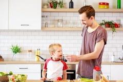 Εικόνα του πατέρα με τα μαγειρεύοντας λαχανικά γιων Στοκ Εικόνα