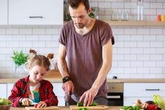 Εικόνα του πατέρα με τα μικρά μαγειρεύοντας λαχανικά κορών Στοκ Εικόνες