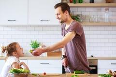 Εικόνα του πατέρα με τα μικρά μαγειρεύοντας λαχανικά κορών Στοκ εικόνα με δικαίωμα ελεύθερης χρήσης