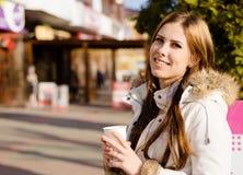 Εικόνα του όμορφου κοριτσιού που φορά το φλυτζάνι εκμετάλλευσης παλτών στοκ εικόνες