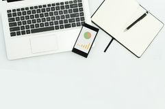Εικόνα του lap-top υπολογιστών, κινητό τηλέφωνο με τη γραφική παράσταση, κενό σημειωματάριο στον εργασιακό χώρο Στοκ φωτογραφίες με δικαίωμα ελεύθερης χρήσης