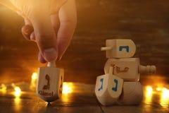 Εικόνα των εβραϊκών διακοπών Hanukkah με την ξύλινα συλλογή & x28 dreidels περιστροφή top& x29  και χρυσά φω'τα γιρλαντών Στοκ Εικόνα