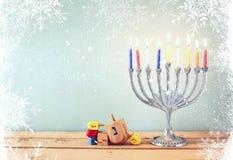 Εικόνα των εβραϊκών διακοπών Hanukkah με το menorah (παραδοσιακά κηροπήγια) και τα ξύλινα dreidels (περιστρεφόμενη κορυφή) Στοκ Εικόνα