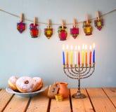 Εικόνα των εβραϊκών διακοπών Hanukkah με το menorah (παραδοσιακά κηροπήγια), donuts και τα ξύλινα dreidels (περιστρεφόμενη κορυφή Στοκ Εικόνες
