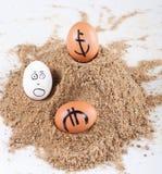Εικόνα των μεγάλων άσπρων αυγών με τα ευρο- σημάδια dollarand σε μια άμμο Στοκ Φωτογραφία