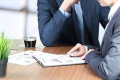 Εικόνα των συνέταιρων που συζητούν τα έγγραφα και τις ιδέες στη συνεδρίαση Στοκ Εικόνες
