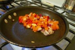 Εικόνα των τεμαχισμένων καρυκευμάτων σε ένα τηγανίζοντας τηγάνι στοκ εικόνα