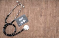 Εικόνα υπερήχου μωρών και stetoscope στο ξύλινο υπόβαθρο Στοκ Φωτογραφίες