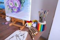 Εικόνα φωτογραφιών που χρωματίζεται από τον καλλιτέχνη και τις στάσεις easel στο στήριγμα τέχνης Στοκ Εικόνες