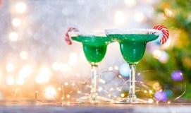 Εικόνα Χριστουγέννων δύο γυαλιών κρασιού με το πράσινο κοκτέιλ, ραβδιά καραμέλας Στοκ Εικόνες