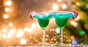 Εικόνα Χριστουγέννων δύο γυαλιών κρασιού με το πράσινο κοκτέιλ, ραβδιά καραμέλας Στοκ Εικόνα