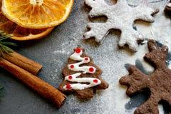Εικόνα Χριστουγέννων Χριστουγεννιάτικα δέντρα και snowflakes μελοψωμάτων σοκολάτας που ψεκάζονται με το αλεύρι σε ένα σκοτεινό υπ Στοκ Εικόνες